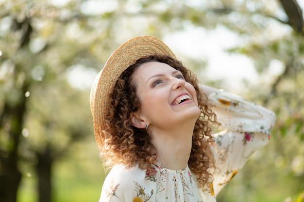 La mujer atractiva joven del retrato con el pelo rizado en sombrero de mimbre elegante disfruta del jardín verde floreciente en día de primavera.