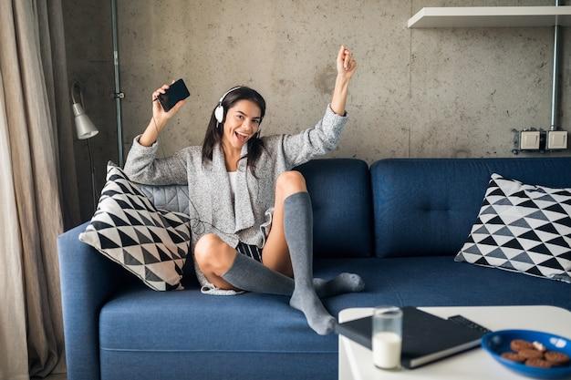Mujer atractiva joven en ropa casual relajante en casa, tiempo libre, divertirse, sonriendo escuchando música en auriculares, bailando sentado en el sofá, alegre, feliz, con medias, suéter