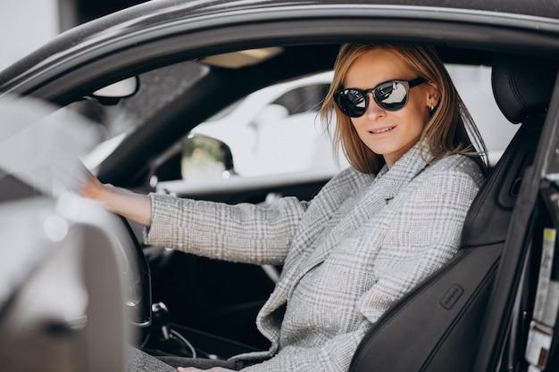 Mujer atractiva joven sentada en un auto