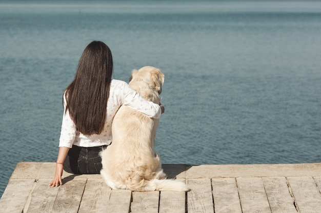 Mujer atractiva joven sentada en el muelle con su perro. mejores amigos al aire libre