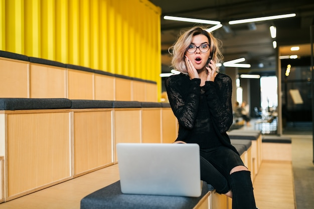 Mujer atractiva joven sentada en la sala de conferencias trabajando en la computadora portátil con gafas, auditorio moderno, educación estudiantil en línea, expresión de la cara sorprendida