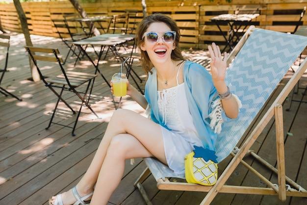 Mujer atractiva joven sentada en la tumbona en traje de moda de verano, vestido blanco, capa azul, gafas de sol, sonriendo, bebiendo limonada, accesorios elegantes, relajantes vacaciones