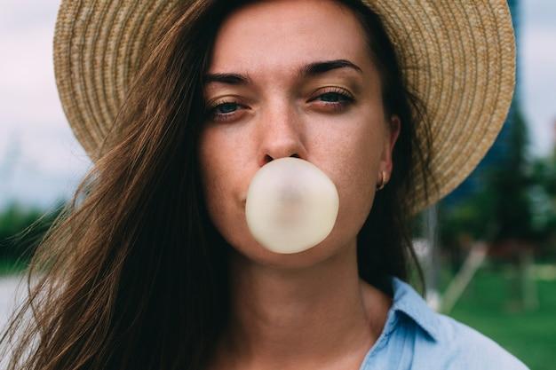 Mujer atractiva joven con sombrero soplando burbujas de chicle en la calle