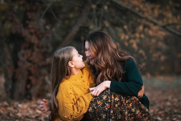 Mujer atractiva joven en suéter verde y falda larga y linda chica adolescente en suéter amarillo con largo cabello rubio pasar tiempo juntos en el parque de otoño. copia espacio