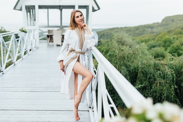 Mujer atractiva, joven con teléfono en las manos en la terraza de verano en las montañas. tiempo de belleza. concepto de mañana