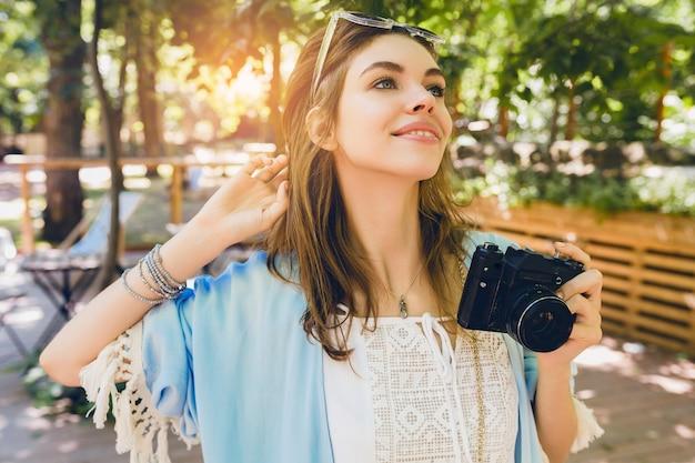 Mujer atractiva joven en traje de moda de verano tomando fotografías con cámara retro