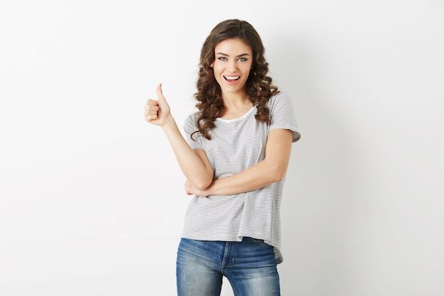 Mujer atractiva joven vestida con camiseta casual y jeans mostrando gesto positivo, sonriente, feliz, estilo hipster, aislado, rizado, pulgar hacia arriba
