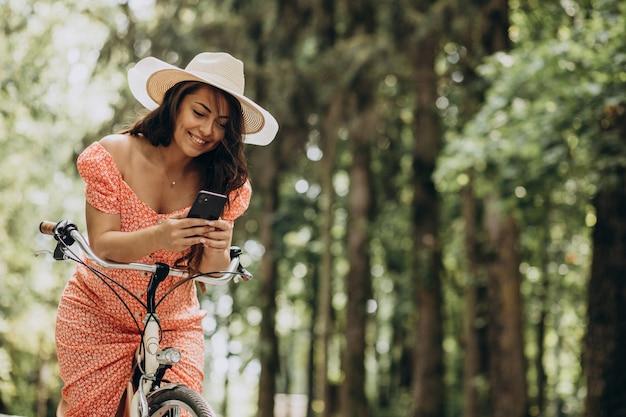 Mujer atractiva joven en vestido montando bicicleta y usando el teléfono