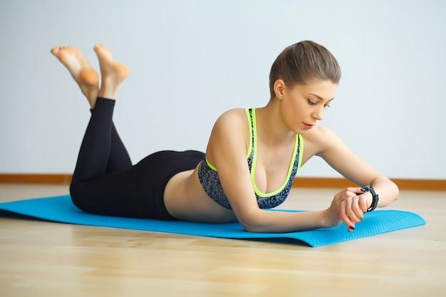 Mujer atractiva joven yogui practicando concepto de yoga, vistiendo ropa deportiva, camiseta negra y pantalones largos