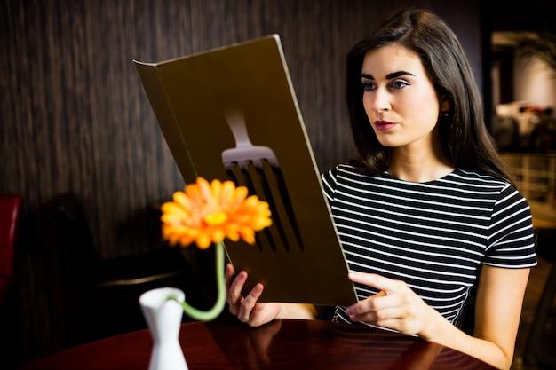 Mujer atractiva leyendo el menú en el restaurante.