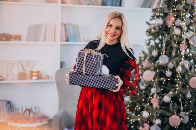 Mujer atractiva madura que sostiene los regalos de navidad por el árbol de navidad