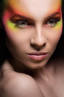 Mujer atractiva con maquillaje coloreado