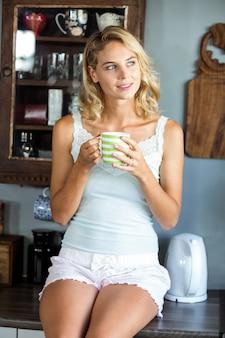 Mujer atractiva mirando a otro lado mientras tomando un café en la cocina