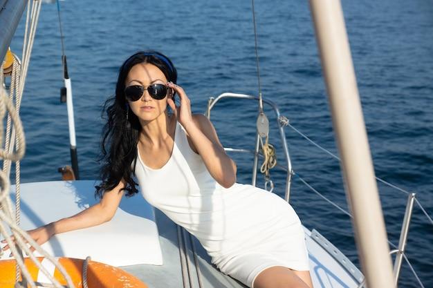 La mujer atractiva de la moda en un vestido blanco está mintiendo en la cubierta de un yate.