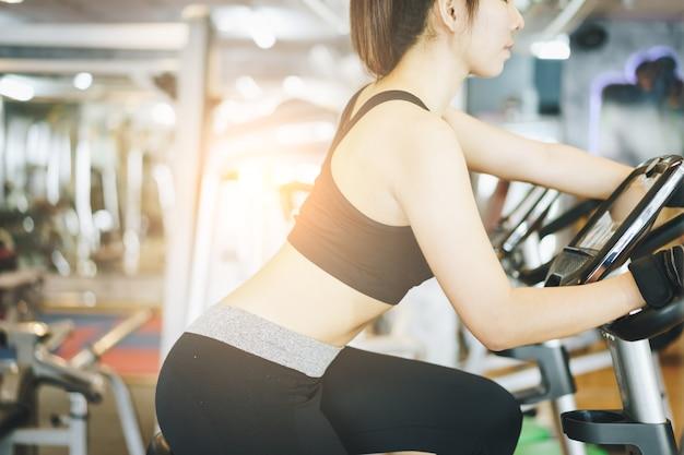 Mujer atractiva montando en la bicicleta de spinning en el gimnasio.