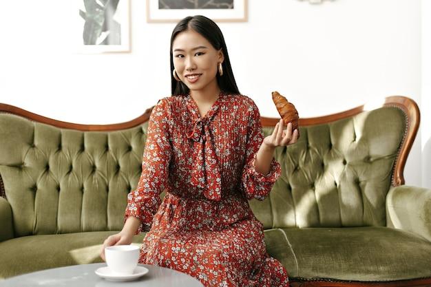 Mujer atractiva morena asiática en elegante vestido floral rojo sonríe sinceramente, se sienta en un sofá verde suave, toma una taza de té y sostiene un croissant