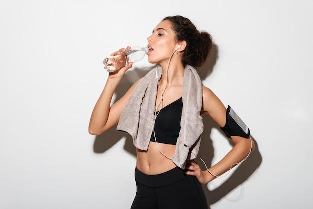 Mujer atractiva morena fitness con toalla sosteniendo el brazo en la cadera