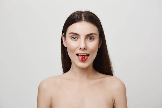 Mujer atractiva mostrando vitaminas en la lengua y sonriendo