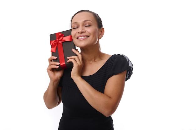 Mujer atractiva con los ojos cerrados vestida de negro posa a la cámara sobre fondo blanco, con una caja de regalo negra cerca de su rostro, sonríe, sonrisa con dientes, disfrutando del presente. viernes negro, concepto de cumpleaños
