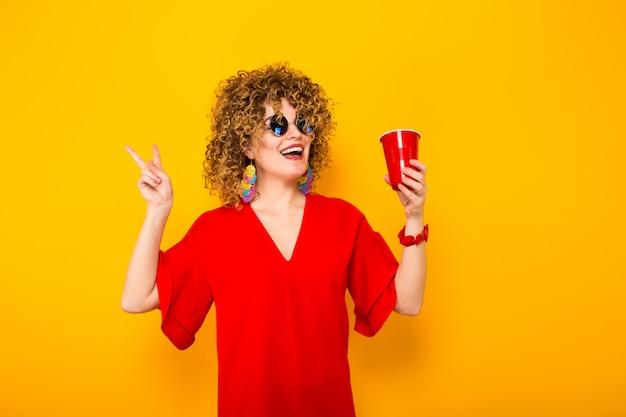 Mujer atractiva con pelo corto y rizado y bebida.