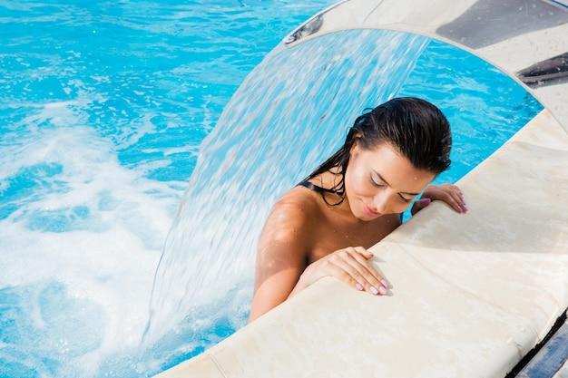 Mujer atractiva de pie en la piscina bajo la cascada