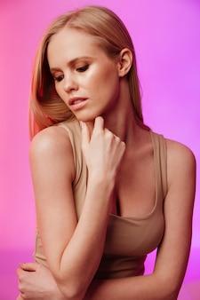 Mujer atractiva de pie y posando sobre pared rosa
