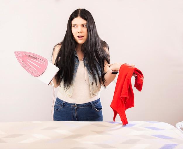 Mujer atractiva planchando ropa con plancha eléctrica aislado