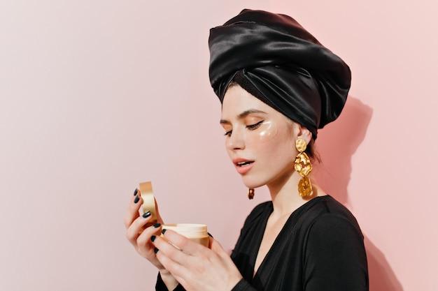 Mujer atractiva posando con crema facial y parches para los ojos