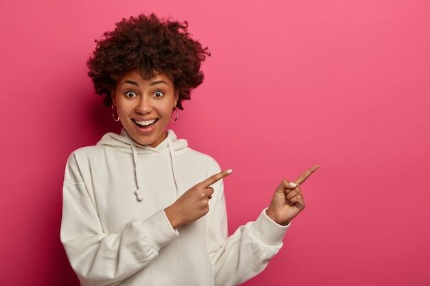 Una mujer atractiva y positiva de piel oscura le pide que siga la página, señala con el dedo a la derecha, recomienda hacer clic en el enlace o visitar la tienda, sonríe alegremente, vestida con una sudadera blanca. publicidad, promoción