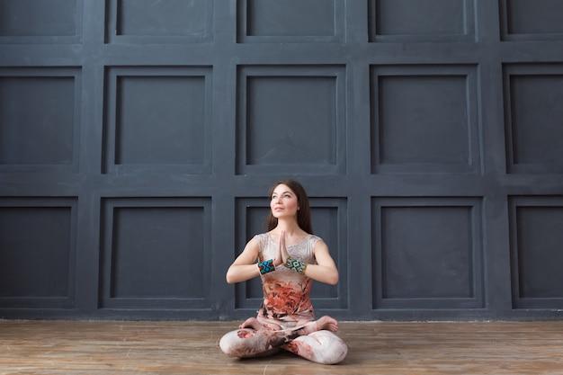 Mujer atractiva practicando yoga, mientras está sentado en postura de loto