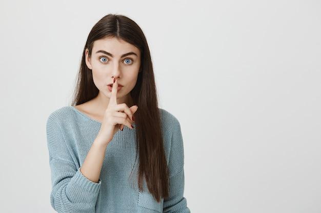 La mujer atractiva presiona el dedo a los labios pidiendo callar, callar