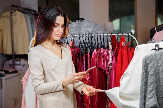 Mujer atractiva que controla código de barras en alameda de compras