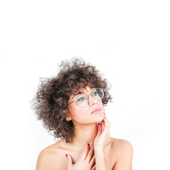 Una mujer atractiva que lleva gafas tocando su mejilla aislada sobre fondo blanco