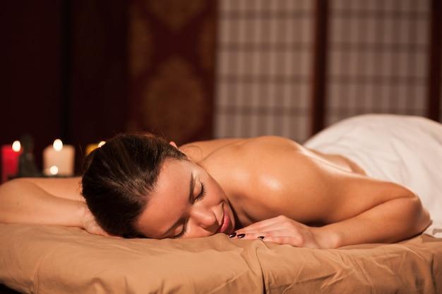 Mujer atractiva que miente en la tabla del masaje en el centro del balneario, espacio de la copia. joven clienta esperando su relajante masaje de cuerpo completo, pasando el día en el salón de mimos. recreación, salud, relajación.