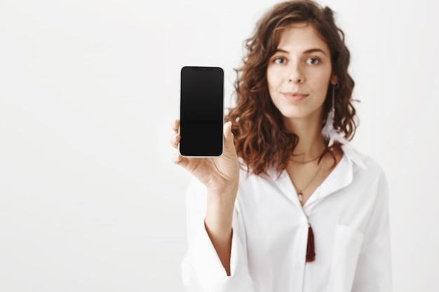Mujer atractiva que muestra una pantalla de teléfono inteligente, aplicación de publicidad