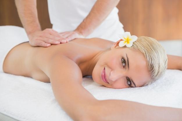 Mujer atractiva que recibe masaje de espalda en el centro de spa