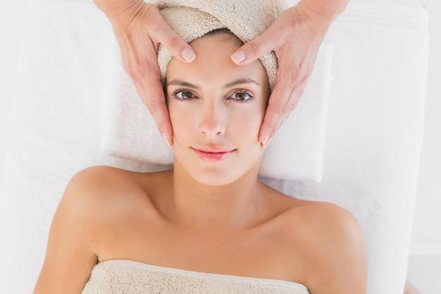 Mujer atractiva que recibe masaje facial en el centro de spa