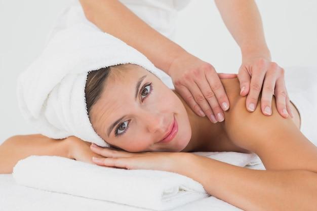 Mujer atractiva que recibe masaje de hombro en el centro de spa