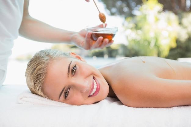 Mujer atractiva que recibe tratamiento de spa con miel