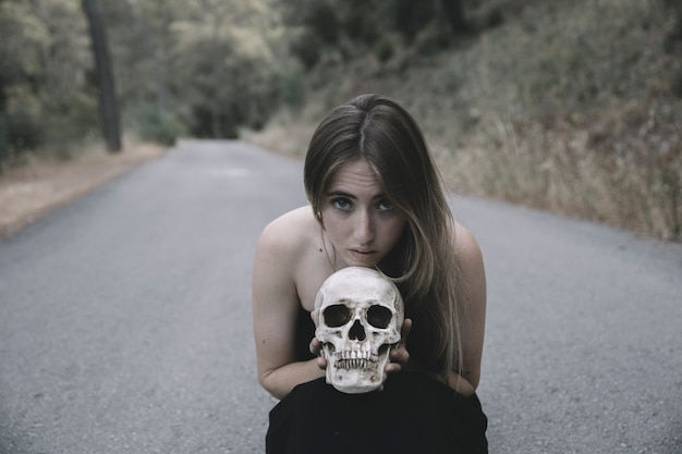 Mujer atractiva que se sienta en el camino y que mira la cámara que sostiene el cráneo decorativo del hombre