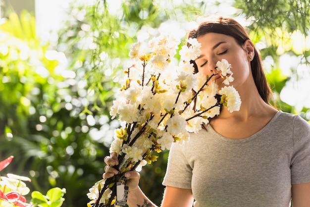 La mujer atractiva que sostiene el manojo de ramitas de la flor acerca a cara