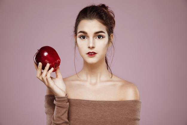 Mujer atractiva que sostiene la manzana roja en rosa