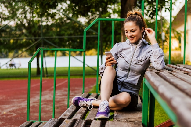 Mujer atractiva que usa un teléfono inteligente mientras está sentado en un banco de madera en un parque