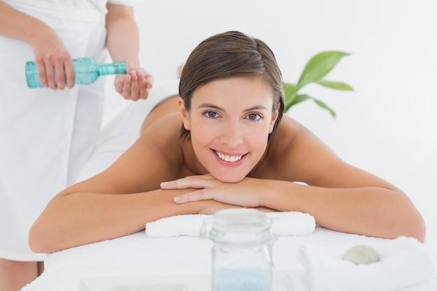 Mujer atractiva recibiendo aceite de masaje en la espalda