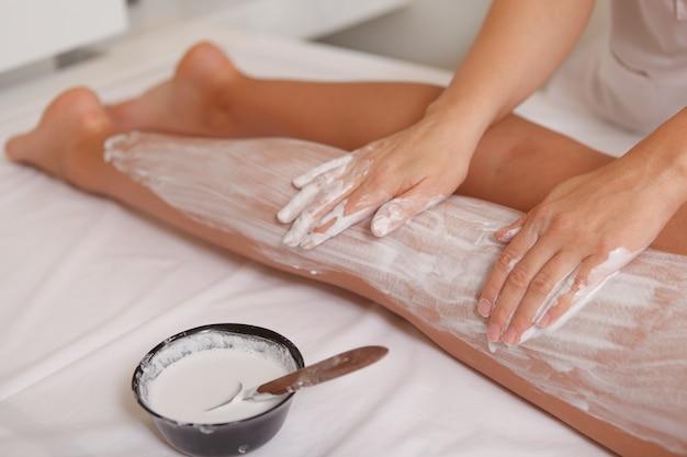 Mujer atractiva recibiendo envolturas corporales con máscara en el centro de spa