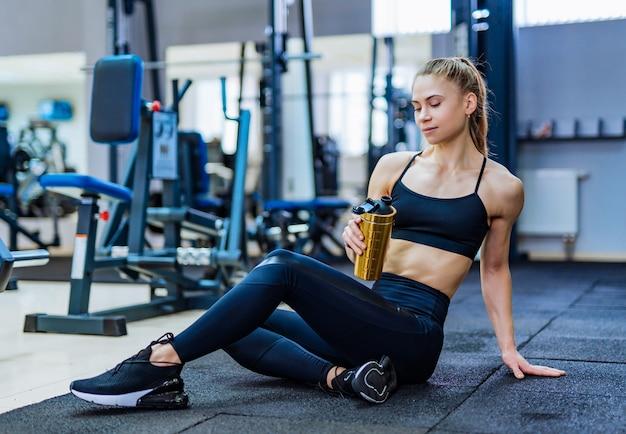 Mujer atractiva en ropa deportiva con botella de agua deportiva en la mano descansando en el piso después de entrenar en el gimnasio.
