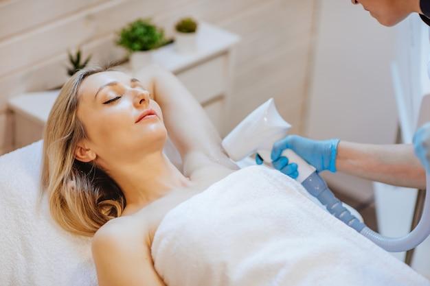 Mujer atractiva rubia en bata de baño blanca recostada en la silla de cosmetología y recibiendo procedimiento de depilación para sus brazos.