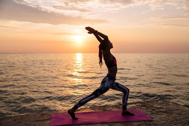 Mujer atractiva saludable haciendo ejercicios para el cuerpo, practicando yoga