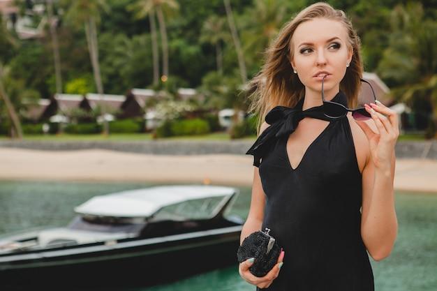 Mujer atractiva sexy de lujo vestida con vestido negro posando en el muelle en el hotel resort de lujo, con gafas de sol, vacaciones de verano, playa tropical