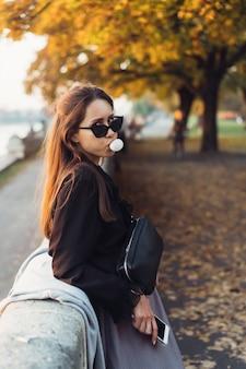 Mujer atractiva con smartphone al aire libre en el parque